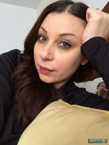 a bored selfie with her head leaning against her arms on bed