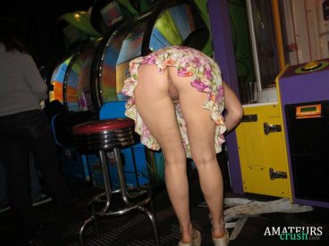 rear pussy showing in arcade hall while she's bent over grabbing her winning lots from the game machine