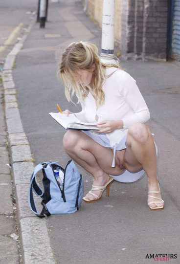 college girl on the ground writing in her agenda having a accidental upskirt moment showing her pussy