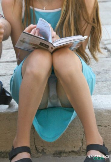 upskirt oops of college girl sitting on the stairs reading a book showing her wet panties