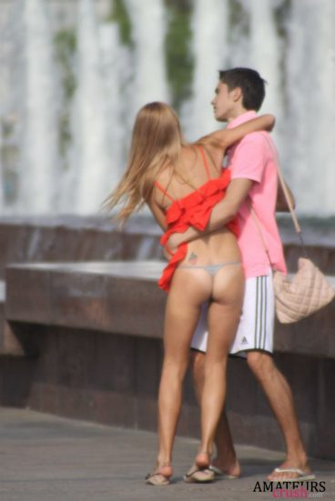 accidental upskirt of couple hugging in public showing tight ass under red dress