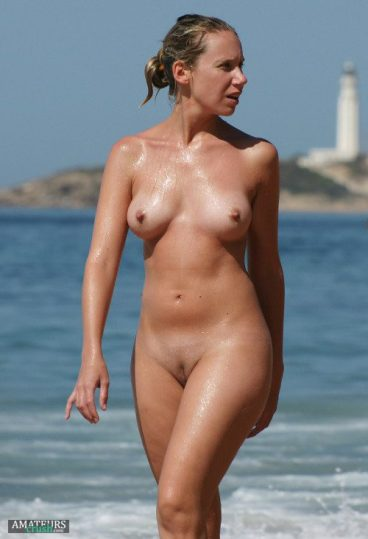 nudist all wet and walking out of the sea with her beautiful tits
