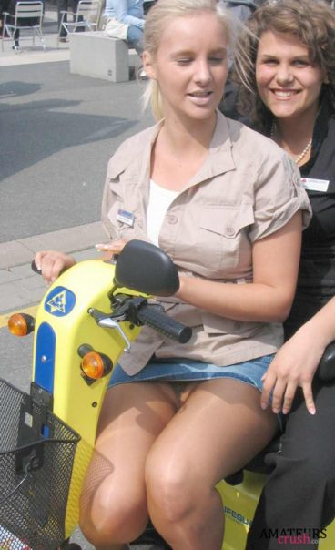 sitting on a scooter with a miniskirt and no panties having a oops upskirt moment with her friend