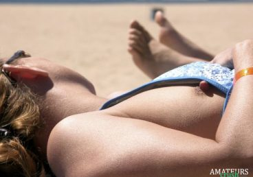 close up of a public nip slip at the beach while tanning