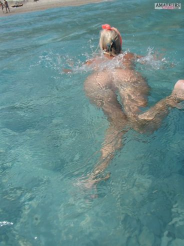 Nude swimming wife with her beautiful big butt just under the water surface at the beach