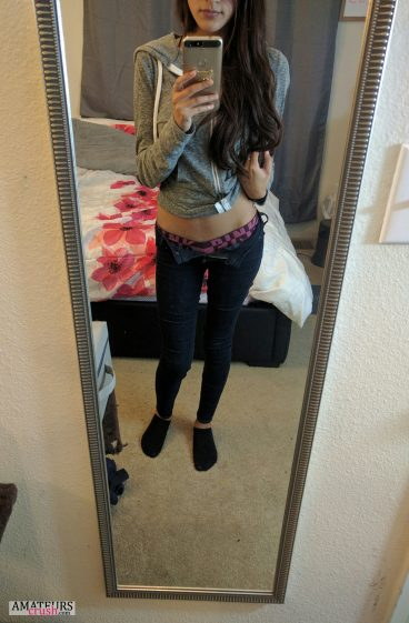 College girl making teasing selfie with her pants button open