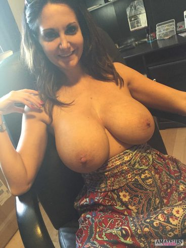 Humongous boobs out of dress of sexy mom in chair