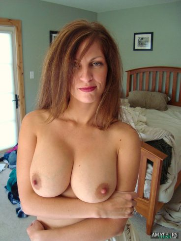 Unimpressed MILF looking at camera with her big boobs