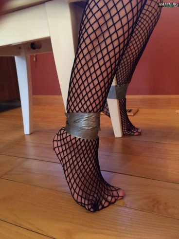 Upclose fishnet stockings and legs tied up with ducktape against chair