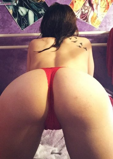 Bent over girl in red thong showing her beautiful delicious ass on bed