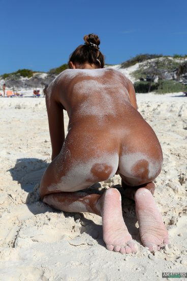 Bent over girlfriend showing her tight ass covered in sand on beach