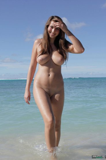 Busty naked girl on naked beach walking out of the sea
