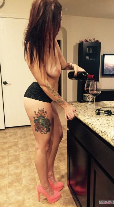 Sexy wife pouring wine in glass with no bra