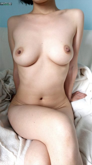 Nude Julia sitting on bed with her legs crossed and showing her big tits