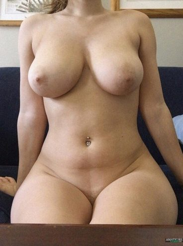 Sexy amateur with curves sitting naked on couch